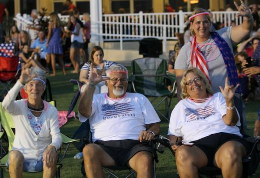 Group of residents signing I Love You in Sign Language during 4th of July celebration.